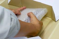 Ręka mężczyzna chwyta bąbla opakunek dla Pakować i ochrona produktu, pękał zdjęcie stock