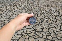 ręka mężczyzna trzyma pękającą ziemię w kraju i kompas obrazy stock