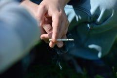 Ręka mężczyzna trzyma papieros w ręce outside, na backgrou Zdjęcie Stock