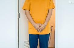 Ręka mężczyzny mienia crotch, Męska potrzeba siusiać przy toaletą, rak prostaty fotografia royalty free