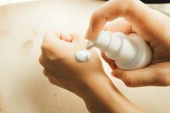Ręka młoda kobieta chwyta kremowa butelka i prasa na górze guzika Fotografia Royalty Free