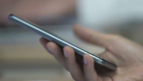Ręka młodej kobiety mienia smartphone, kciuka scrolling strony internetowe na ekranie sensorowym zdjęcie wideo