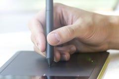 Ręka młody człowiek pisze na grafiki pastylce obraz royalty free