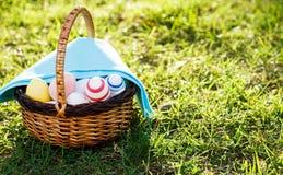 Ręka malował Wielkanocnych jajka w rattan koszu na zielonej trawie z błękitnym ręcznikiem Tradycyjna dekoracja dla wielkanocy prz fotografia royalty free