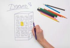 Ręka malująca na rysunkowym papierze z kredki kondygnaci budynkiem, światło w mieszkaniu i inskrypcja, marzymy Zdjęcie Royalty Free