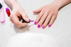 Ręka maluje gwoździe, gel purpury, gel gwoździa manicure zdjęcie royalty free