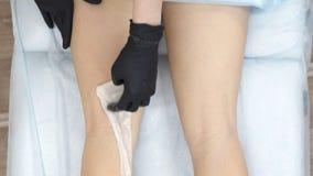 Ręka mistrz shugaring czarne rękawiczki i gwałtowny ostrożnie stosowaliśmy białego specjalnego wosk na ciekach dziewczyna zdjęcie wideo