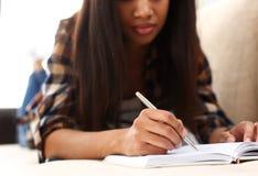 Ręka murzynka pisze opowieści w notatniku zdjęcia stock