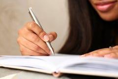 Ręka murzynka pisze opowieści w notatniku zdjęcie royalty free