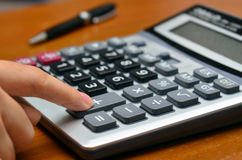 Ręka na kalkulatorze (Kalkulować biznes, biuro przedmioty,) obraz stock