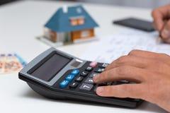 Ręka na kalkulatorze - kalkulować gospodarstwo domowe koszty Fotografia Stock