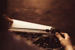 Ręka na maszyna do pisania i prześcieradle biały papier na drewnianym tle styl retro obraz stock