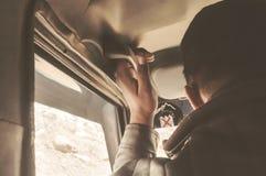 Ręka na rękojeści Piękny młodego człowieka obsiadanie na frontowych miejsce pasażera samochód wzdłuż autostrady podróży Cieszy si zdjęcia stock