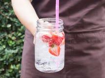 Ręka na słuzyć szkle lukrowy truskawkowy sodowany napój Zdjęcia Stock