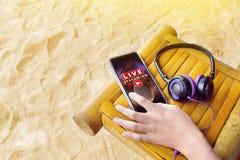 Ręka na telefonie komórkowym z muzyka na żywo hełmofonami i lać się obraz stock