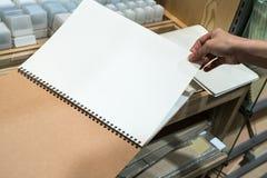 Ręka obraca pustą stronę notatnik przy materiały sklepem fotografia royalty free