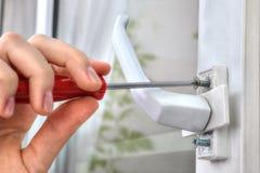 Ręka odśrubowywa rygiel, używać śrubokręt, uninstall nadokiennych brzęczenia Obrazy Stock