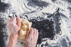 Ręka odgórny widok ugniata ciasto na czarnym tle zdjęcie royalty free