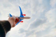 Ręka osoba trzyma zabawkarskiego samolot przeciw niebieskiemu niebu i biel chmurnieje Pojęcie wolność, lot i podróż, zdjęcia stock