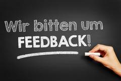 Ręka pisze w Niemieckiej ` Wir gryźć informacje zwrotne um! ` Zdjęcia Stock
