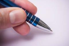 ręka pisze z błękitnym piórem na purpurowym tle mężczyzna obraz stock