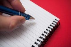 ręka pisze z błękitnym piórem na spirales nutowej książce na czerwonym tle mężczyzna zdjęcia stock