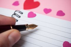 ręka pisze z rocznika piórem na spirales nutowej książce z papierowymi sercami na różowym tle mężczyzna fotografia stock