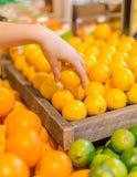 Ręka podnosi up cytrynę w produkt spożywczy sekci sklep spożywczy obraz stock