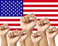 Ręka podnosząca up zaciskająca pięść na usa flaga Zdjęcie Stock