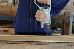 Ręka pracownik musztruje dziury z drewnianą deską używać elektrycznego świderu maszynę w warsztacie Zdjęcia Royalty Free