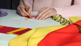 Ręka projektant rysuje nakreślenie suknia na płótno stole dla dostosowywać, z bliska zbiory wideo