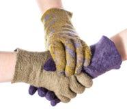 Ręka przymocowywa uścisk dłoni ręki w barwionych rękawiczkach zdjęcia stock