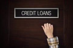 Ręka puka na Kredytowych pożyczkach drzwiowych Zdjęcie Royalty Free