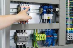 Ręka punkty w kierunku switchboard lub kontrolnego gabineta - elektronika zdjęcia royalty free