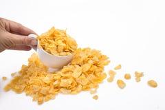 Ręka Rozlewa Kukurydzanych płatki z Malutkiej filiżanki Obrazy Stock