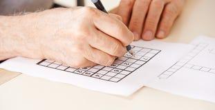 Ręka rozwiązuje sudoku starszy mężczyzna Obrazy Royalty Free