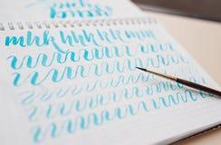 Ręka rysująca piszący list tło Pisać list szczotkarską kaligrafię na papierze Zdjęcie Royalty Free