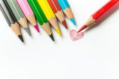 Ręka rysujący doodle czerwony kierowy rząd stubarwni ołówki na białej księgi tle Walentynki matki dnia rodzina obrazy stock