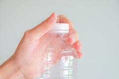 Ręka skręta butelka z popielatym tłem Obraz Stock