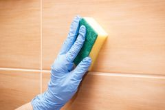 Ręka starsza kobiety obcierania i domycia łazienka tafluje używać gąbkę, gospodarstwo domowe obowiązków pojęcie zdjęcie royalty free