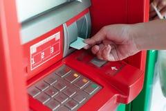 Ręka stawia banka ATM kartę w ATM banka maszynę wycofywać pieniądze Fotografia Stock