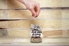 Ręka stawia monetę w szklanym słoju z wpisowym ` na nowego domu ` na drewnianym tle, fotografia stock