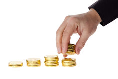Ręka stawia monety w stertę monety Zdjęcia Royalty Free
