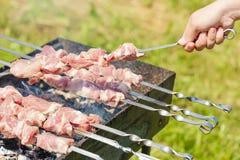 Ręka stawia skewer z kawałkami mięso dla shish kebabu grilla na outdoors grillu z zielonym rozmytym tłem Obraz Stock