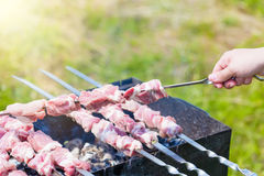 Ręka stawia skewer z kawałkami mięso dla shish kebabu grilla na outdoors grillu z zielonym rozmytym tłem Zdjęcie Royalty Free