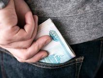 Ręka stawiający ruble w cajg kieszeni Obrazy Stock