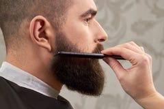 Ręka szczotkuje brodę fryzjer męski Fotografia Stock