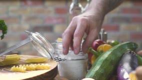 Ręka szefa kuchni kucbarski bierze solankowy nękanie dla solić jedzenie podczas gdy gotujący na kuchennej kuchni Szefa kuchni pek zbiory wideo