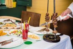 Ręka szefa kuchni szef kuchni z nożem czyści mięso od skewer zdjęcie royalty free