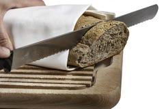 Ręka tnący chleb na drewnianym talerzu Zdjęcia Stock